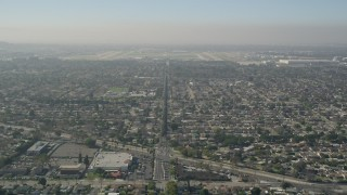 AX0016_105 - 5K stock footage aerial video tilt from East Warlow Road through neighborhoods to reveal and approach Long Beach Airport, California