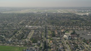 AX0016_106 - 5K stock footage aerial video tilt up East Warlow Road to reveal and approach neighborhoods and Long Beach Airport, California