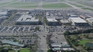 AX0016_110 - 5K stock footage aerial video fly over parking garage to approach Long Beach Airport and terminals, California