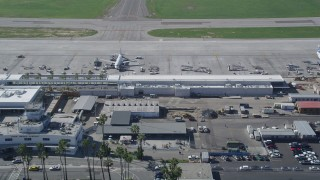 AX0016_111 - 5K stock footage aerial video approach and fly over commercial jet at a terminal at Long Beach Airport, California