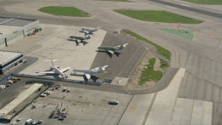 AX0016_112 - 5K stock footage aerial video of civilian jets parked near a hangar at Long Beach Airport, California