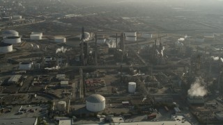 AX0017_005 - 5K stock footage aerial video of flying by an oil refinery and smoke stacks, Carson, California