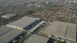 AX0017_007 - 5K stock footage aerial video fly over warehouses toward a residential neighborhood, Carson, California