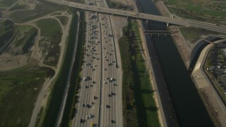 AX0017_024 - 5K stock footage aerial video of following heavy interstate traffic along the river, Carson, California