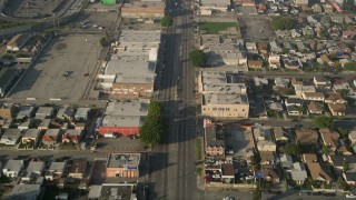 AX0017_036 - 5K stock footage aerial video of following a city street past apartment buildings, South Central Los Angeles