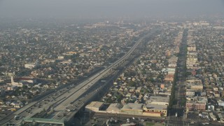 AX0017_039 - 5K stock footage aerial video of Interstate 110 with traffic, tilt to reveal neighborhoods, South Central Los Angeles