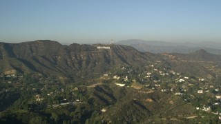 AX0017_086 - 5K stock footage aerial video of homes and apartment buildings in the hills, reveal Hollywood Sign, Hollywood, California