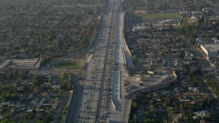 AX0017_117 - 5K stock footage aerial video of following heavy interstate traffic through neighborhoods, Pacoima, California, sunset