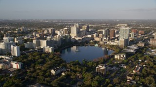 AX0018_003 - 5K stock footage aerial video of approaching Downtown Orlando and Lake Eola at sunrise in Florida