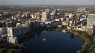 AX0018_004 - 5K stock footage aerial video fly over Lake Eola to approach buildings in Downtown Orlando at sunrise, Florida