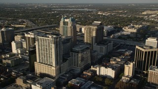 AX0018_004E - 5K stock footage aerial video fly over Lake Eola to approach office buildings and arena in Downtown Orlando at sunrise, Florida