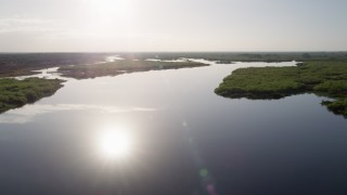 AX0018_043 - 5K stock footage aerial video fly low altitude over St. Johns River near Orlando at sunrise, Florida