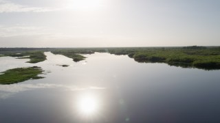 AX0018_045 - 5K stock footage aerial video of flying low over St. Johns River near Orlando, Florida at sunrise