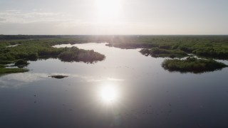 AX0018_046 - 5K stock footage aerial video of flying low altitude over St. Johns River by Orlando at sunrise in Florida