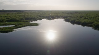 AX0018_047 - 5K stock footage aerial video fly low over bank of St. Johns River by Orlando at sunrise in Florida
