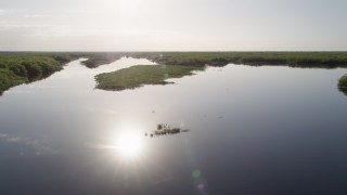 AX0018_049 - 5K stock footage aerial video of flying low altitude over St. Johns River near Orlando at sunrise in Florida