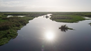 AX0018_050 - 5K stock footage aerial video of flying over St. Johns River near Orlando at sunrise, Florida
