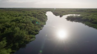 AX0018_051 - 5K stock footage aerial video of following St. Johns River near Orlando at sunrise in Florida
