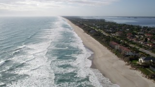 AX0018_070 - 5K stock footage aerial video of following the beach by Melbourne Beach, Florida