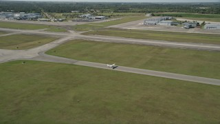 AX0018_101 - 5K stock footage aerial video approach small airplane at St. Lucie County International Airport in Florida