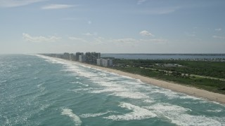 AX0019_007 - 5K stock footage aerial video of Jensen Beach apartment buildings by the beach in Florida