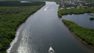 AX0019_010 - 5K stock footage aerial video fly over sailboat on Indian River to approach speedboat in Hobe Sound, Florida