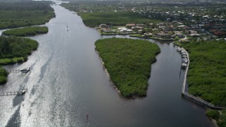 AX0019_013 - 5K stock footage aerial video fly over Indian River and pan to approach waterfront homes in Hobe Sound, Florida