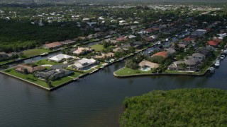 AX0019_014 - 5K stock footage aerial video pass waterfront neighborhoods on canals by the Indian River in Hobe Sound, Florida