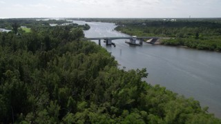 AX0019_017 - 5K stock footage aerial video fly over mangroves to approach small bridge over the Indian River in Florida