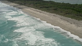 AX0019_033 - 5K stock footage aerial video of waves lapping beach in Tequesta, Florida