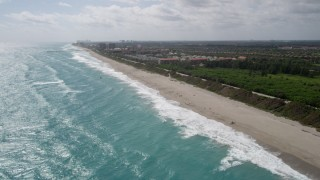 AX0019_041 - 5K stock footage aerial video approach kite surfer by the beach in Jupiter, Florida