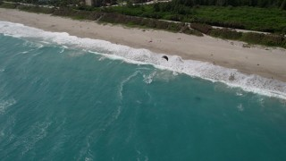 AX0019_042 - 5K stock footage aerial video flyby kite surfer near the beach in Jupiter, Florida