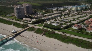 AX0019_044 - 5K stock footage aerial video of sunbathers on the beach and beachfront homes in Juno Beach, Florida