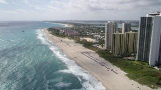 AX0019_049 - 5K stock footage aerial video approach parasailer by beachfront condominiums in Riviera Beach, Florida