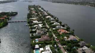 AX0019_064 - 5K stock footage aerial video fly over lakefront mansions on a small Palm Beach Island, Florida