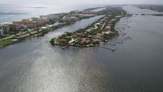 AX0019_074 - 5K stock footage aerial video approach lakefront Palm Beach mansions with docks on a Florida island