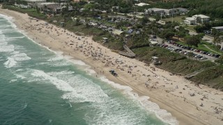 AX0019_085 - 5K stock footage aerial video of approaching a beach with sunbathers in Boynton Beach, Florida