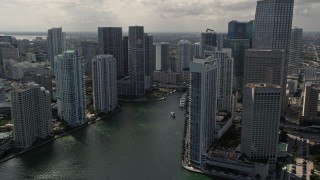 AX0020_026E - 5K stock footage aerial video tilt from fishing boats in the bay to reveal skyscrapers and river in Downtown Miami, Florida