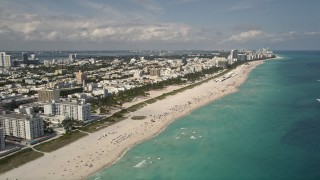 AX0020_044 - 5K stock footage aerial video tilt from sunbathers on the beach to a wider view of South Beach, Florida