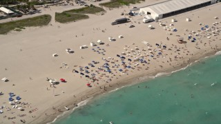 AX0020_046 - 5K stock footage aerial video of sunbathers enjoying the beach and ocean in South Beach, Florida