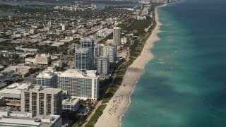 AX0020_063 - Aerial stock footage of Flyby Beachfront Hotels and Tilt to Sunbathers in Miami Beach
