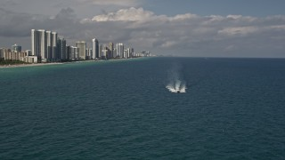 AX0020_072 - 5K stock footage aerial video approach a yacht racing across calm ocean near Sunny Isles Beach, Florida