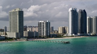 AX0020_076 - 5K stock footage aerial video of a pier by oceanfront condominium complex and hotel in Sunny Isles Beach, Florida
