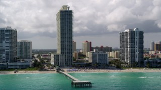 AX0020_077 - 5K stock footage aerial video flyby pier, beachfront condo complex and hotel in Sunny Isles Beach, Florida