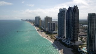 AX0020_085 - 5K stock footage aerial video approach oceanfront hotels and high-rises while flying over the coast in Sunny Isles Beach, Florida
