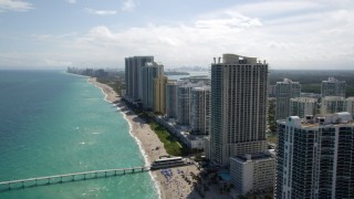 AX0020_086 - 5K stock footage aerial video fly over beach and pier by oceanfront hotel and high-rises in Sunny Isles Beach, Florida