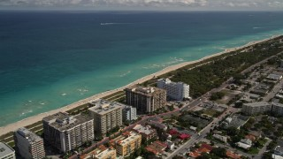 AX0020_096 - 5K stock footage aerial video of oceanfront apartments and beach by a park in Surfside, Florida