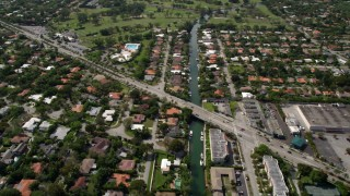 AX0020_102 - 5K stock footage aerial video follow canal through waterfront suburbs and pan across boulevard to reveal country club in Miami Shores, Florida