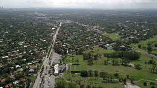 AX0020_103 - 5K stock footage aerial video of boulevard through suburban neighborhoods near golf course in Miami Shores, Florida