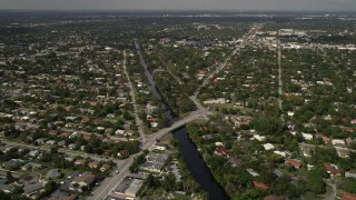 AX0020_104 - 5K stock footage aerial video of canal beside school and suburban neighborhoods in Biscayne Park, Miami, Florida